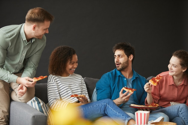 Wieloetniczna grupa przyjaciół jedzących pizzę i przekąski, ciesząc się imprezą w domu, siedząc na dużej kanapie