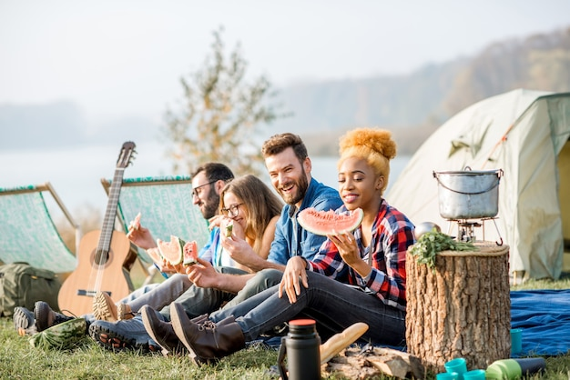 Wieloetniczna grupa przyjaciół na pikniku, jedząca arbuza podczas rekreacji na świeżym powietrzu z namiotem, samochodem i sprzętem turystycznym w pobliżu jeziora