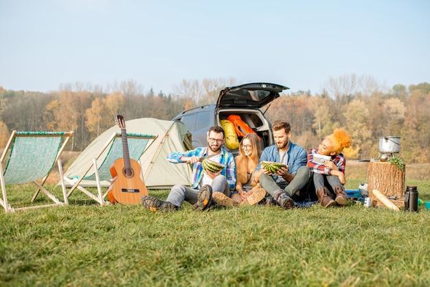 Wieloetniczna grupa przyjaciół na pikniku, jedząca arbuza, siedząca w rzędzie na kempingu z namiotem, samochodem i sprzętem turystycznym w pobliżu jeziora