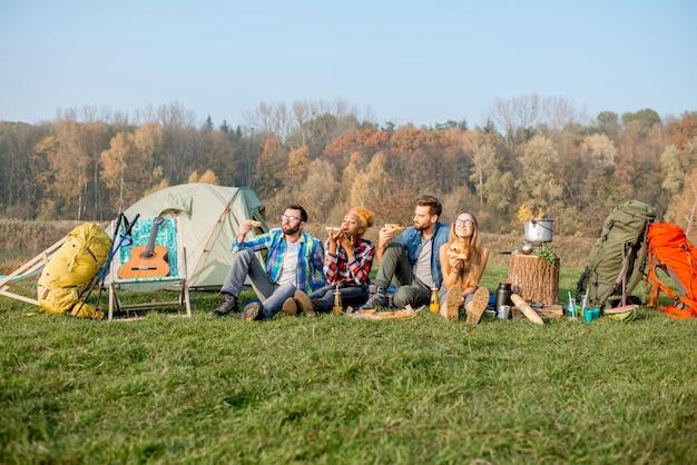 Wieloetniczna grupa przyjaciół na pikniku, jedząca pizzę, siedząca w rzędzie na kempingu z namiotem i sprzętem turystycznym w pobliżu lasu