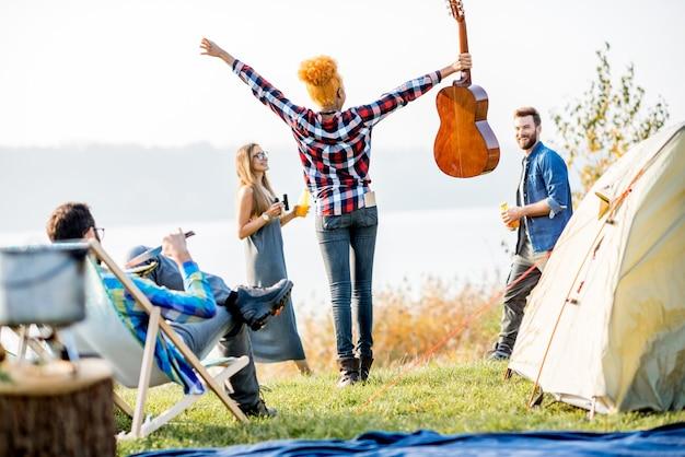Wieloetniczna grupa przyjaciół ubrana niedbale bawiąca się podczas rekreacji na świeżym powietrzu na kempingu nad jeziorem