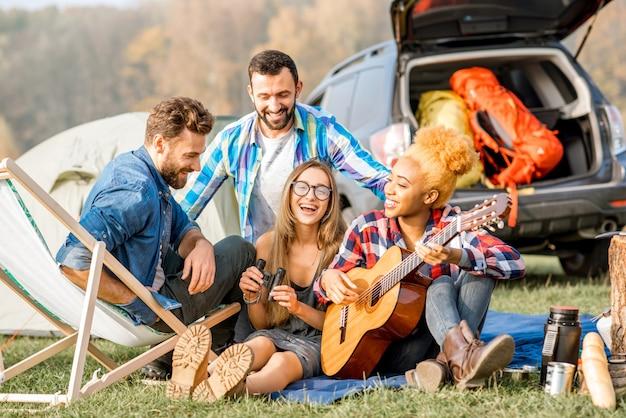 Wieloetniczna grupa przyjaciół ubrana swobodnie, bawiąca się grając na gitarze podczas rekreacji na świeżym powietrzu z namiotem nad jeziorem