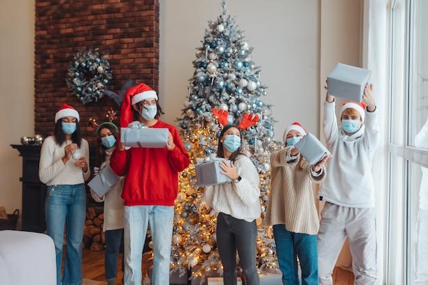 Wieloetniczna grupa przyjaciół w czapkach mikołaja z prezentami w rękach.