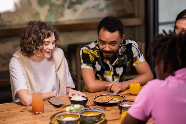 Wieloetniczna grupa studentów mających posiłek w kawiarni