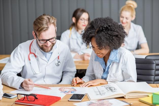 Wieloetniczna grupa studentów medycyny na jednolitym egzaminie pisemnym siedząca w nowoczesnej klasie