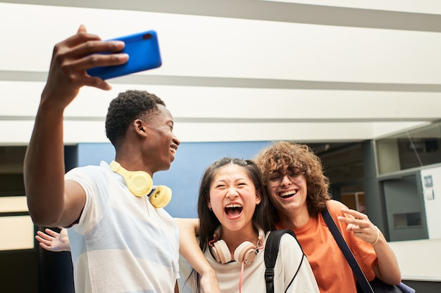 Wieloetniczna grupa studentów robi sobie selfie w koledze z klasy, bawiąc się razem