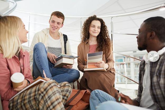Wieloetniczna grupa studentów siedząca na schodach w college'u i rozmawiająca podczas pracy domowej