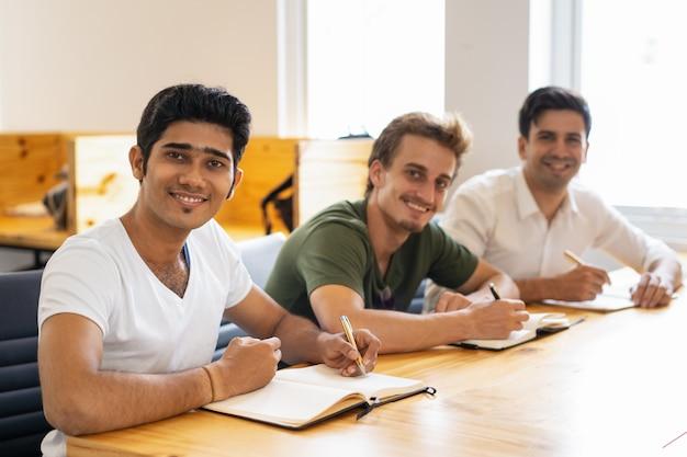 Wieloetniczna grupa szczęśliwi ucznie pozuje w sala lekcyjnej