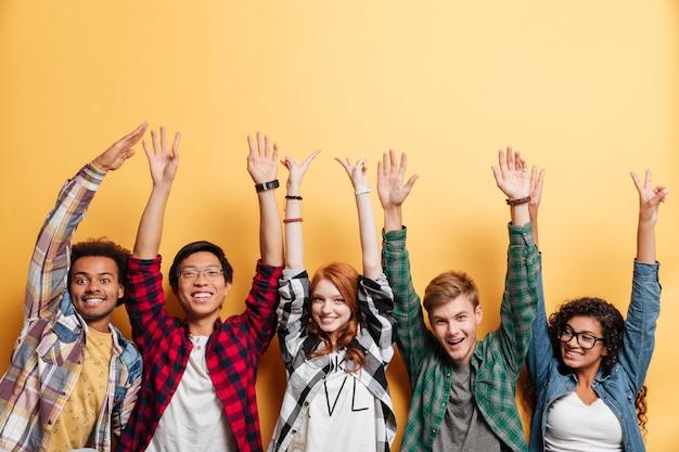 Wieloetniczna grupa szczęśliwych młodych ludzi stojących i świętujących sukces z uniesionymi rękami na żółtym tle