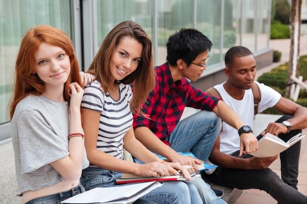 Wieloetniczna grupa szczęśliwych młodych studentów siedzących i rozmawiających na świeżym powietrzu
