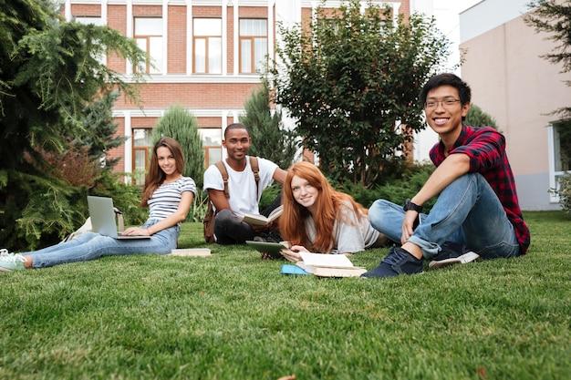 Wieloetniczna grupa uśmiechniętych młodych ludzi siedzących i studiujących na trawniku na świeżym powietrzu