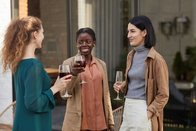 Wieloetniczna grupa współczesnych dorosłych kobiet rozmawiających przy winie na imprezie plenerowej,