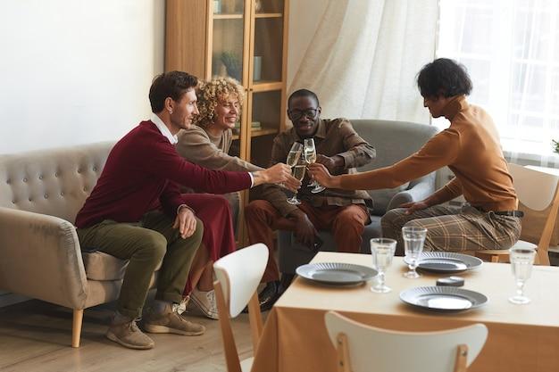 Wieloetniczna grupa współczesnych dorosłych ludzi brzęczących kieliszkami do szampana podczas kolacji w pomieszczeniu z przyjaciółmi,
