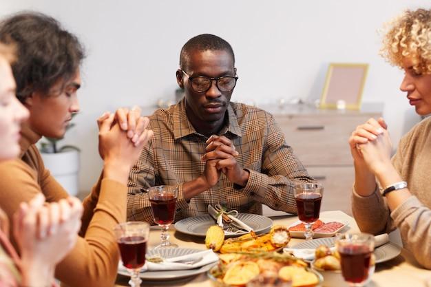 Wieloetniczna grupa współczesnych dorosłych ludzi modlących się z zamkniętymi oczami podczas kolacji z okazji święta dziękczynienia z przyjaciółmi i rodziną