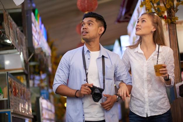 Wieloetniczna młoda para spacerująca ulicą w mieście, do którego podróżowali i robiąca zdjęcia