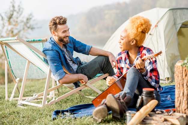 Wieloetniczna para przyjaciół ubrana swobodnie, bawiąca się grając na gitarze podczas rekreacji na świeżym powietrzu z namiotem nad jeziorem