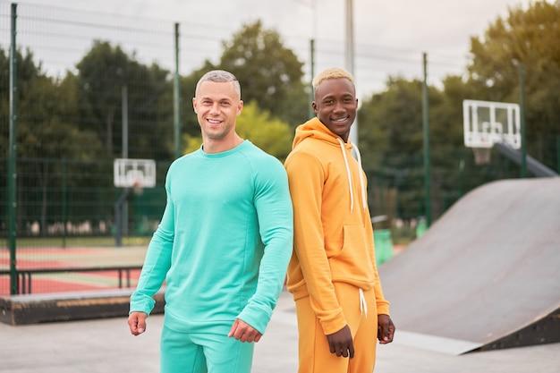 Wieloetniczna przyjaźń czarni afro-amerykańscy i kaukascy przyjaciele spędzają razem czas w skateparku