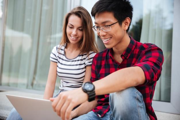 Wieloetniczna szczęśliwa młoda para siedzi i używa laptopa razem na zewnątrz