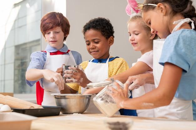 Wieloetniczne dzieci w fartuchach spoglądają na siebie podczas dyskusji na temat świątecznego menu podczas pieczenia ciasteczek