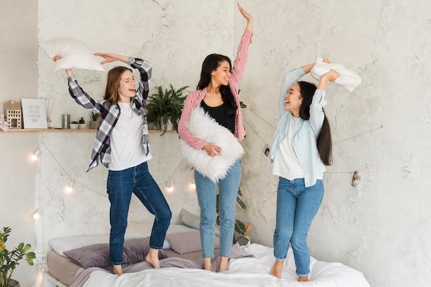 Wieloetniczne dziewczyny bawiące się na łóżku