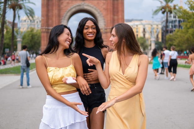 Wieloetniczne dziewczyny rozmawiające na ulicy miasta