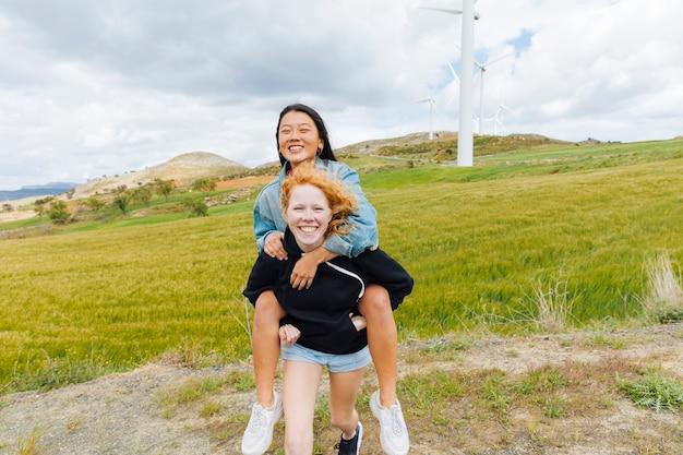 Wieloetniczne kobiety bawiące się w pobliżu farmy wiatrowej