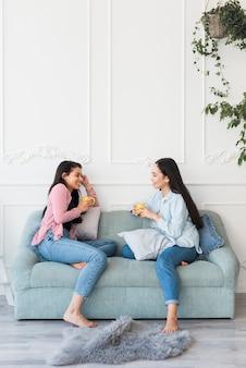 Wieloetniczne kobiety piją herbatę rozmawiają w pokoju