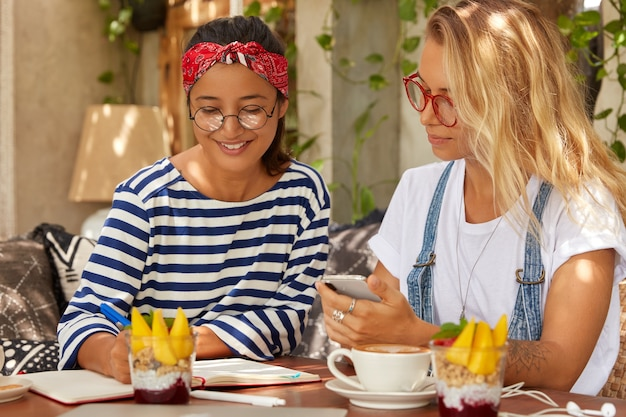 Wieloetniczne kobiety różnych ras omawiają strategię produkcyjną projektu projektowego, zapisują kilka pomysłów w notatniku siedząc w restauracji przy deserze i kawie. azjatycka dziennikarka przeprowadza wywiad
