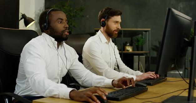 Wieloetniczni dwaj młodzi przystojni operatorzy w zestawach słuchawkowych pracujący przy komputerach i rozmawiający z klientami.