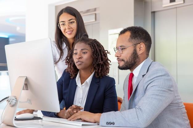 Wieloetniczni koledzy biznesowi za pomocą komputera
