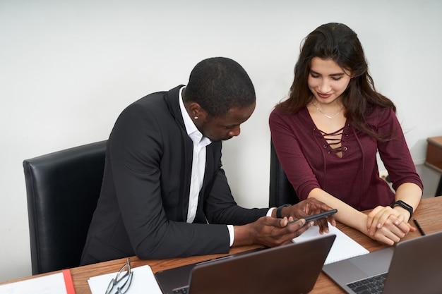 Wieloetniczni koledzy używają telefonów komórkowych i wypróbowują aplikacje na smartfony w biurze