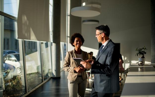 Wieloetniczni ludzie biznesu używa cyfrową pastylkę podczas gdy stojący w biurze