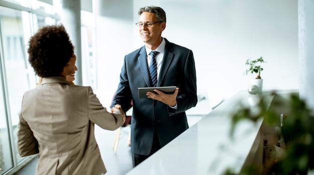 Wieloetniczni ludzie biznesu za pomocą cyfrowego tabletu, stojąc w nowoczesnym biurze