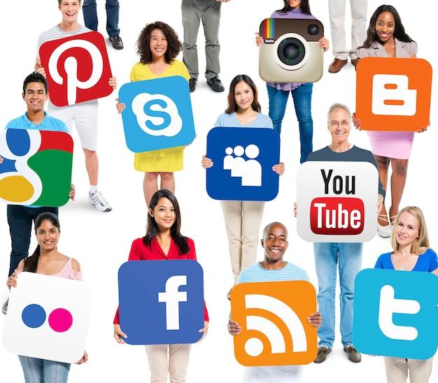 Wieloetniczni ludzie trzymający social networking powiązane logotypy
