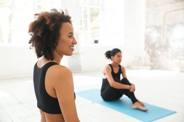 Wieloetniczni ludzie w studio jogi