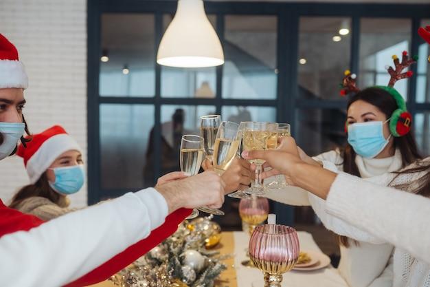 Wieloetniczni młodzi ludzie świętują sylwestra, brzęcząc kieliszkami toastami, wielorasowi przyjaciele bawią się na przyjęciu, gratulują picia szampana