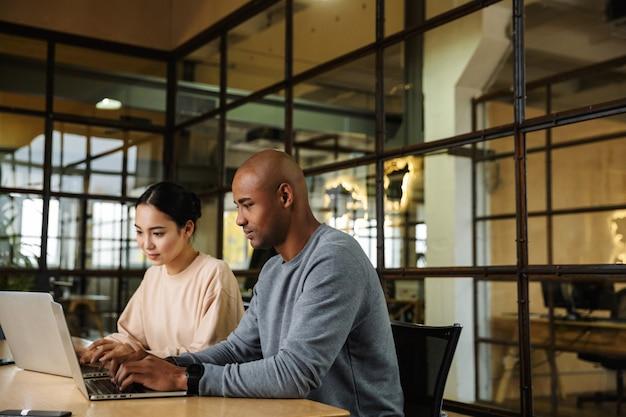 Wieloetniczni młodzi współpracownicy płci żeńskiej i męskiej siedzą przy stole i pracują na laptopach w biurze