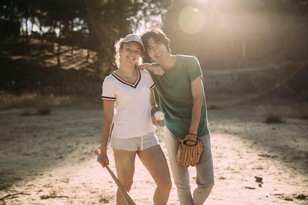 Wieloetniczni nastoletni przyjaciele stoi przy baseballa polem
