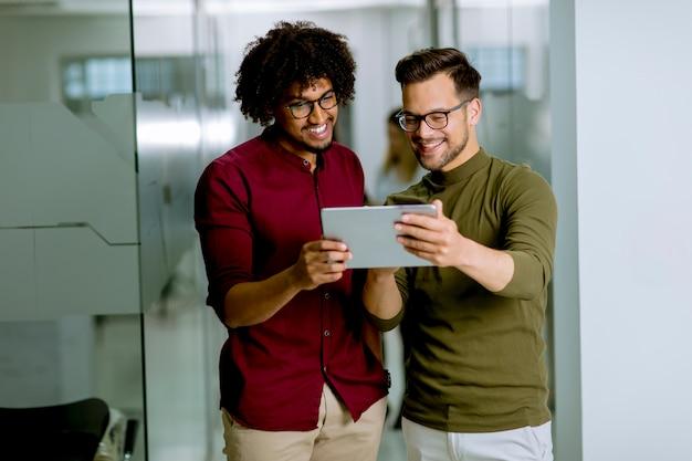 Wieloetniczni partnerzy biznesowi korzystający z cyfrowego tabletu w biurze