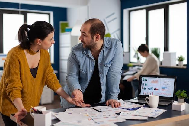 Wieloetniczni przedsiębiorcy przeprowadzają burzę mózgów na wykresach w biurze patrząc na siebie. zróżnicowany zespół ludzi biznesu analizujących z komputera raporty finansowe firmy. udane uruchomienie firmy p