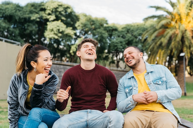Wieloetniczni przyjaciele bawią się siedząc w parku