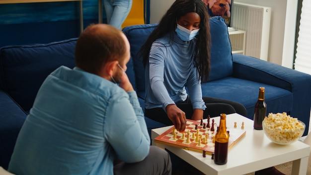 Wieloetniczni przyjaciele grający w szachy w domu w salonie rozmawiają, zachowując dystans społeczny, aby zapobiec chorobie z covid19 podczas globalnej pandemii, nosząc maskę na twarz. różnorodni ludzie korzystający z gier planszowych
