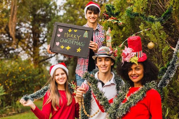 Wieloetniczni przyjaciele na boże narodzenie. wiadomość świąteczna. grupa przyjaciół na choince. koncepcja dekoracji świątecznej.