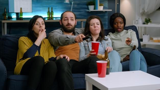 Wieloetniczni przyjaciele odpoczywają na kanapie późno w nocy podczas imprezy domowej