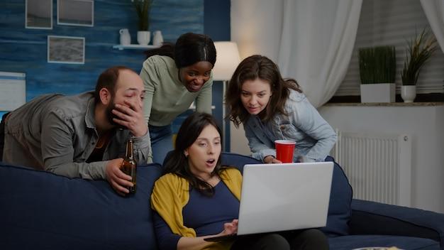 Wieloetniczni przyjaciele oglądają ciekawy film komediowy na laptopie, relaksując się na kanapie, pijąc ...