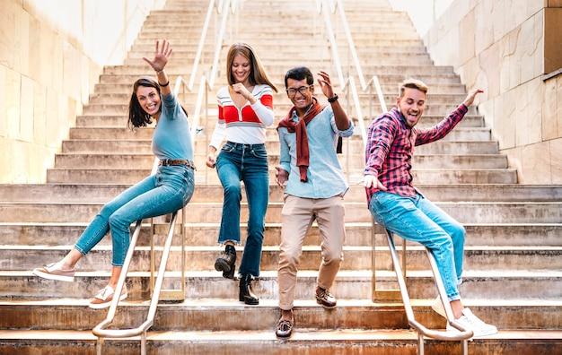 Wieloetniczni przyjaciele schodzą po schodach głupimi zabawnymi ruchami