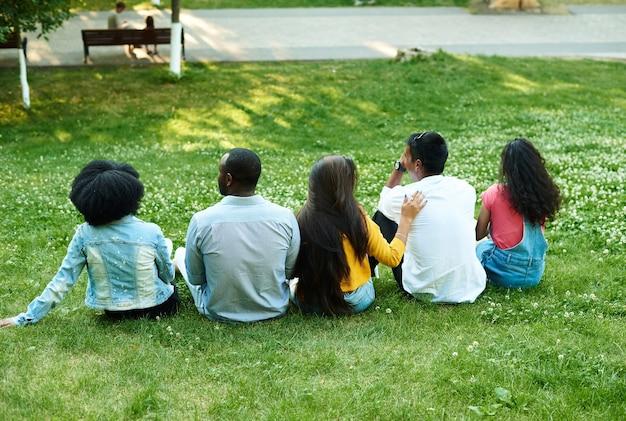 Wieloetniczni przyjaciele siedzą na trawie w parku.