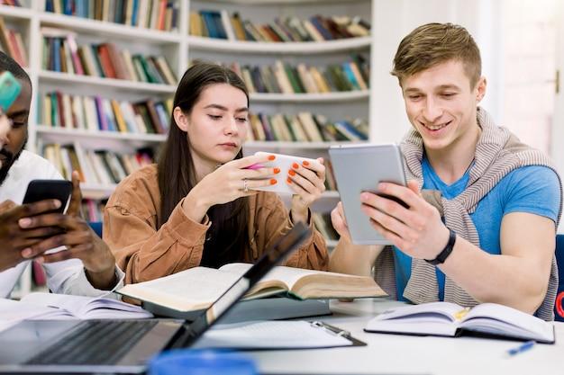 Wieloetniczni przyjaciele, studenci studiują w bibliotece i korzystają z gadżetów, smartfona i tabletu podczas przerwy w przygotowaniach do egzaminów