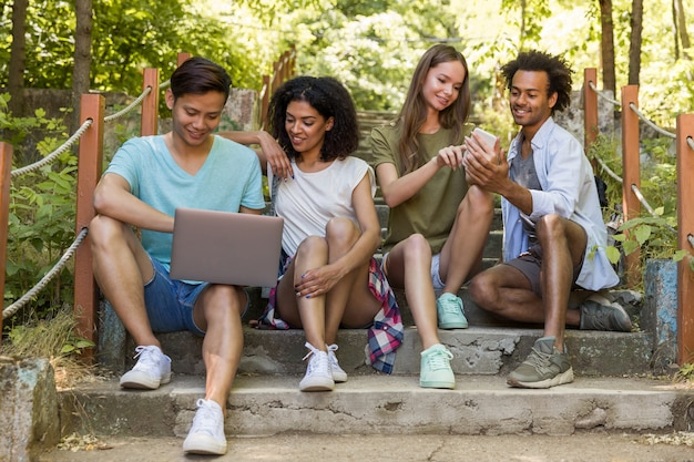 Wieloetniczni przyjaciele uczniowie na zewnątrz za pomocą telefonu komórkowego i laptopa