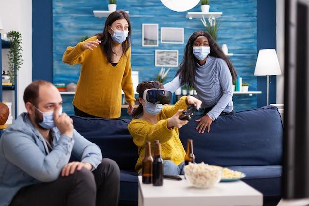 Wieloetniczni różnorodni przyjaciele, którzy korzystają z technologii vr, grając w gry wideo w salonie, nosząc maskę na twarz, aby zapobiec zakażeniu koronawirusem, utrzymując dystans społeczny. obraz koncepcyjny.